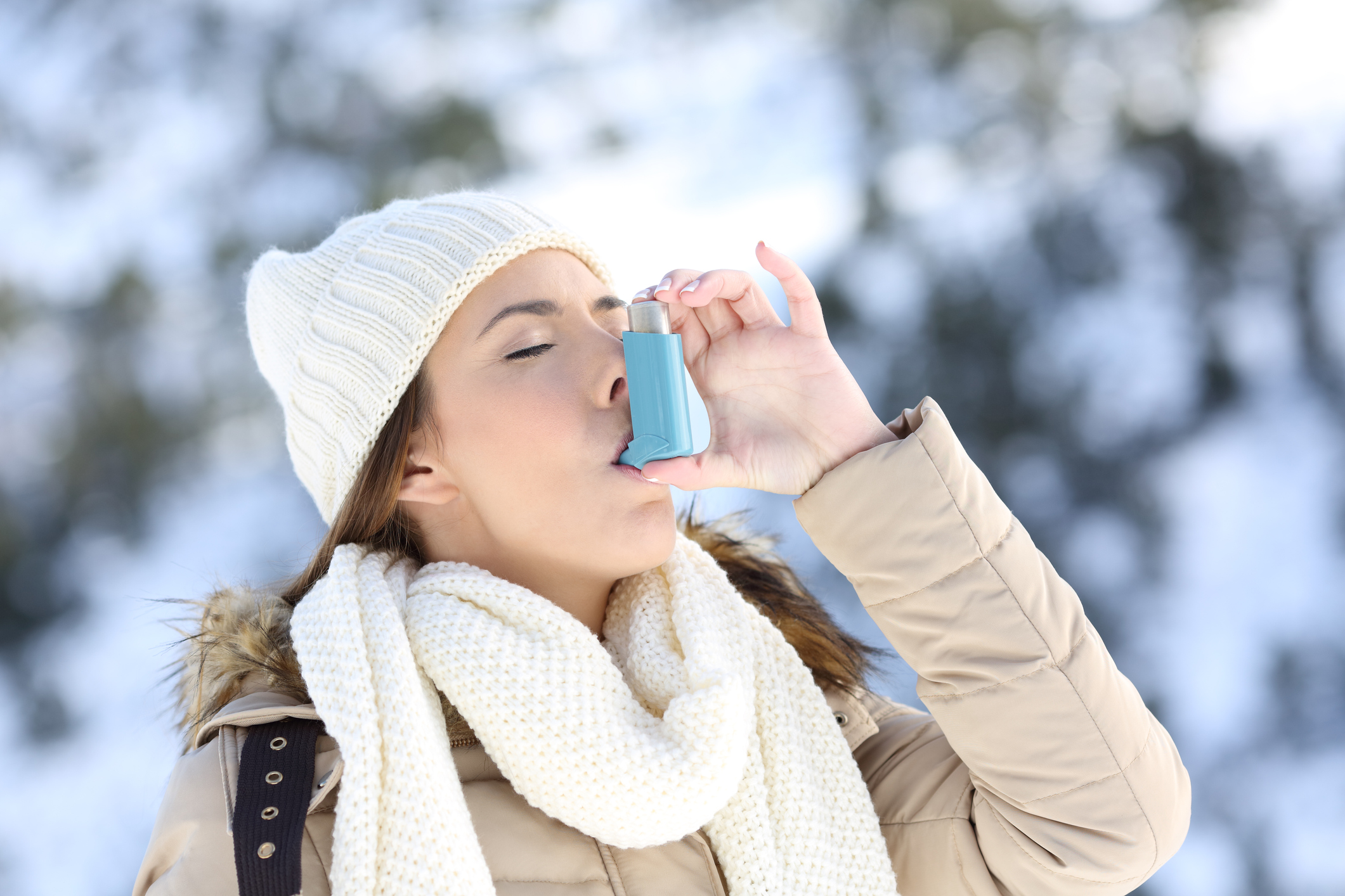Woman using asthma inhaler in a cold winter